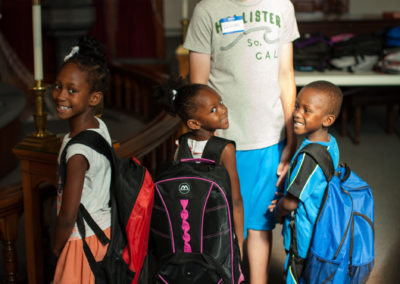 Volunteer standing with kids that received backpacks