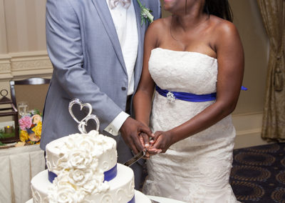 Bride and groom looking at each other while cutting their wedding cake