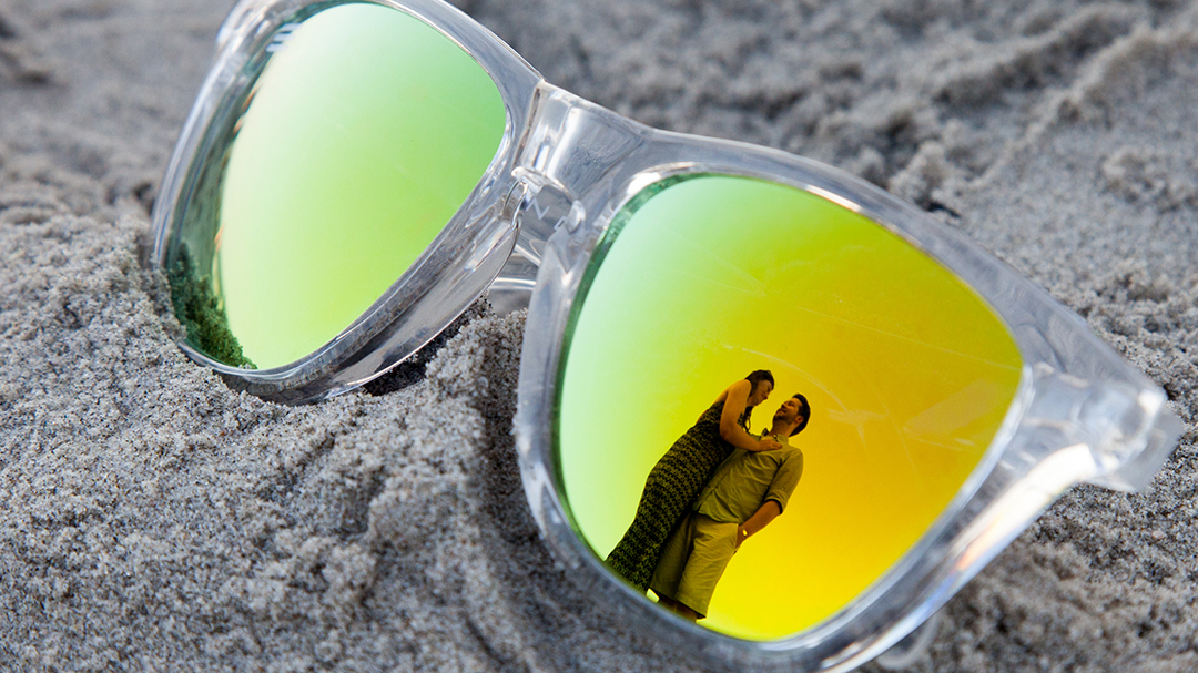 Sunglasses on the beach with the reflection of an engaged couple in them.