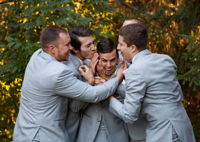 Groom and his groomsmen being funny during their wedding portraits